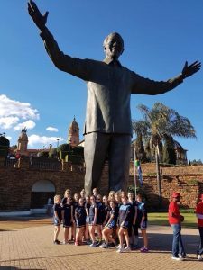 The Rishworth Hockey Team stand around the base of Nelson Mandela's Statue in
