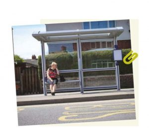 Lady sat a undercover glass bus stop and shelter