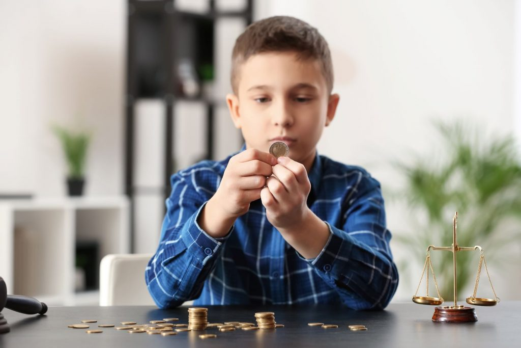 Child sat a table counting money with scales of justice to his side on the table